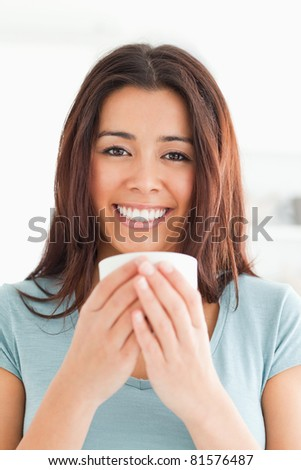 Portrait of a good looking woman enjoying a cup of coffee in the kitchen