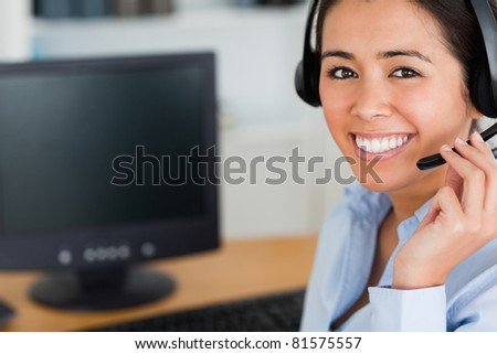 Portrait of a good looking woman wearing a headset and discussing while sitting at the office - stock photo