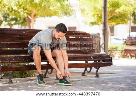 Portrait of a good looking young man tying his shoes and getting ready to go jogging in a park