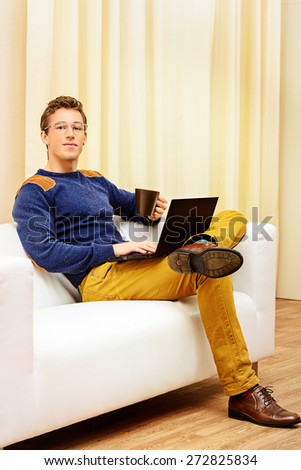 Portrait of a goodlooking smiling young man sitting on a couch at home and working on his laptop.  - stock photo