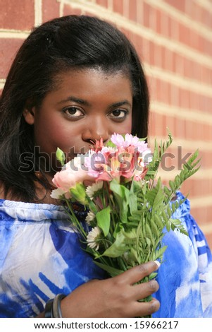 Portrait of a gorgeous african-American young woman with flowers, in an outdoor setting with a bunch of flowers