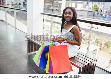 Portrait of a gorgeous black african americcan woman sitting with colorful shopping bags.