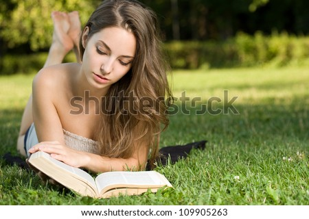Portrait of a gorgeous brunette woman reading a  book in the park.