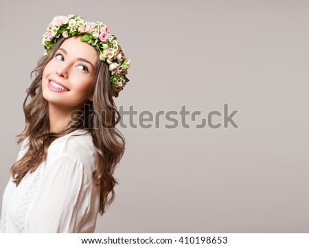 Portrait of a gorgeous brunette woman wearing spring flower wreath.