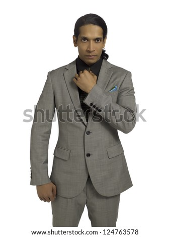 Portrait of a gorgeous businessman looking at the camera while standing on a white surface