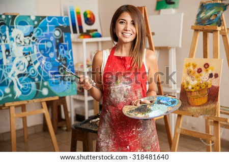 Portrait of a gorgeous female artist working on several art projects on her studio - stock photo