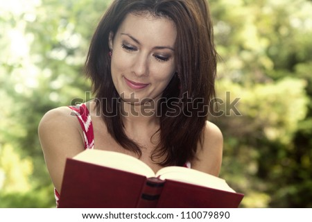 Portrait of a gorgeous girl reading a book in the park.