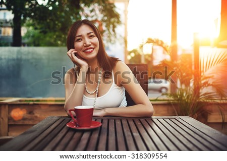 Portrait of a gorgeous happy young asian woman sitting in a cozy sidewalk cafe smiling  to the camera, attractive female enjoying sunny afternoon in modern coffee shop with amazing sunset in summer - stock photo