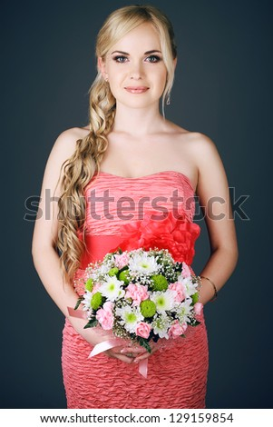 Portrait of a gorgeous long-haired blonde bridesmaid holding a wedding bouquet and posing over dark grey (blue) background. Studio shot