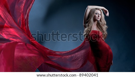 Portrait of a gorgeous sexy blonde with long beautiful hair and body wrapped in red silk, like a flower - stock photo