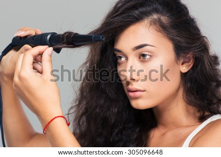 Portrait of a gorgeous woman doing hairstyle with hair straightener over gray background. Looking away