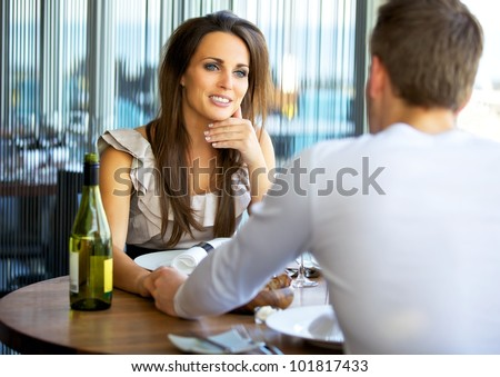 Portrait of a gorgeous woman holding hands with her boyfriend at a fancy restaurant