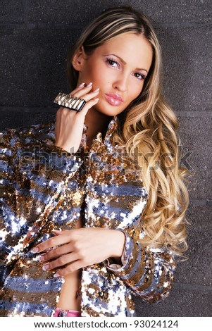 Portrait of a gorgeous woman in golden clothing and accessories - stock photo