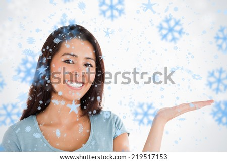 Portrait of a gorgeous woman showing a copy space while standing against snowflakes