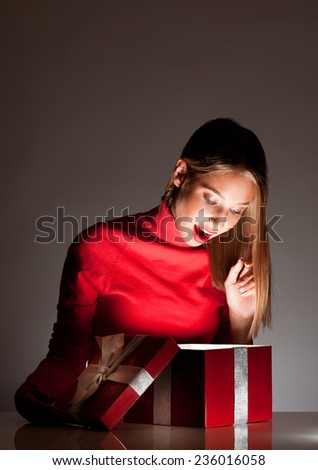 Portrait of a gorgeous young blond woman with bright red gift box. - stock photo