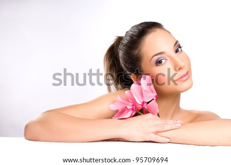 Portrait of a gorgeous young brunette spa girl with pink flowers. - stock photo