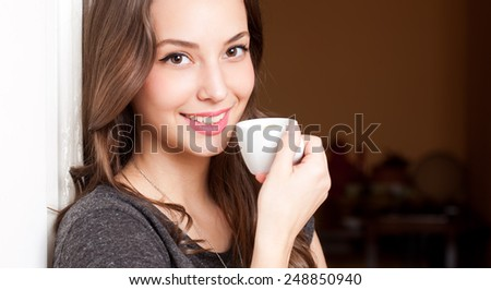 Portrait of a gorgeous young brunette woman having coffee. - stock photo