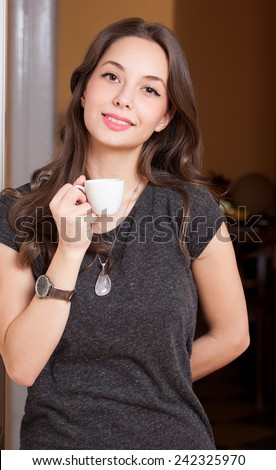 Portrait of a gorgeous young brunette woman holding cup of coffee. - stock photo
