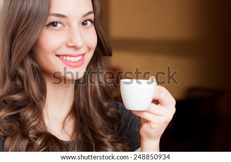 Portrait of a gorgeous young brunette woman holding cup of coffee.