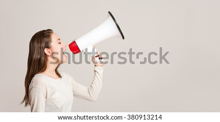 Portrait of a gorgeous young brunette woman holding megaphone. - stock photo