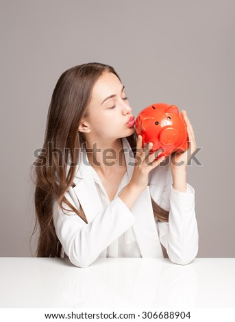 Portrait of a gorgeous young brunette woman holding piggy bank. - stock photo