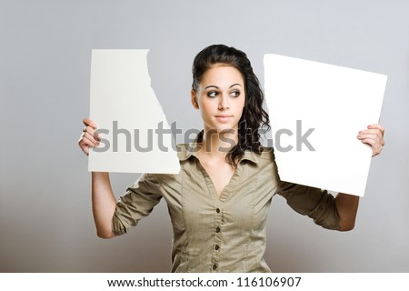 Portrait of a gorgeous young brunette woman holding two halves of torn apart blank white billboard.