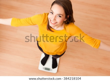 Portrait of a gorgeous young brunette woman standing on a scale. - stock photo