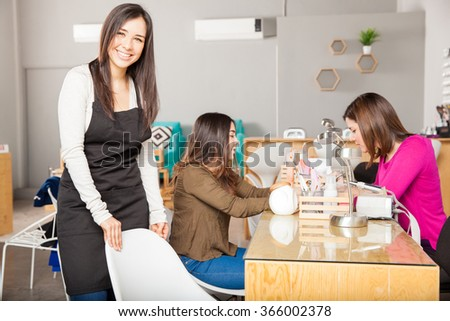 Portrait of a gorgeous young business owner inviting her customers to sit in a chair at her nail and beauty spa - stock photo