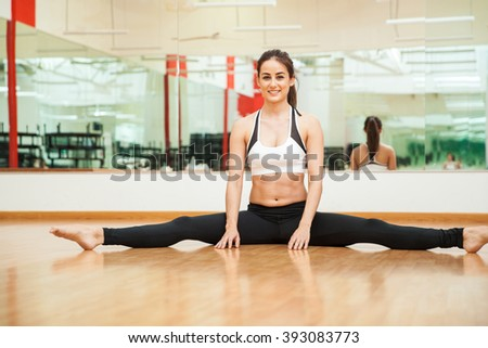 Portrait of a gorgeous young Hispanic brunette doing a leg split at the gym and smiling