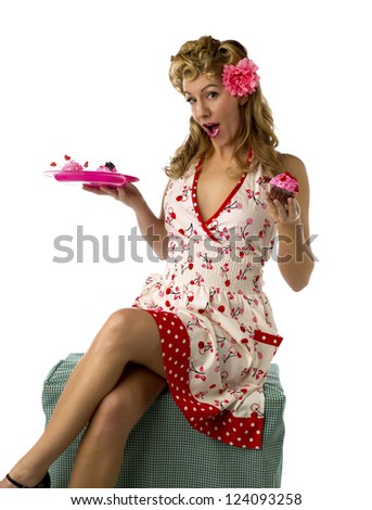 Portrait of a gorgeous young woman holding a plate of cupcakes with mouth open