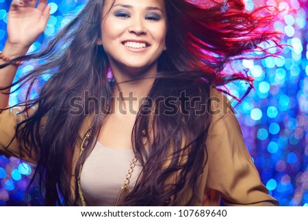 Portrait of a gorgeous young woman in motion against sparkling background - stock photo