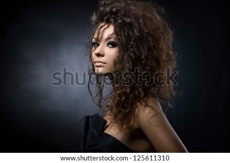 portrait of a gorgeous young woman on dark background - stock photo