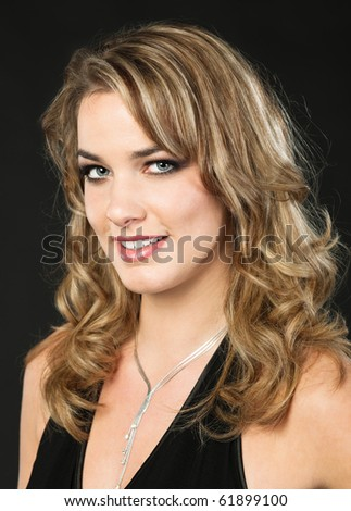 Portrait of a gorgeous young woman on dark barkground - stock photo