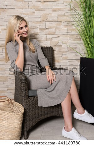 Portrait of a gorgeous young woman talking on her cell phone while sitting alone in a waiting area,beautiful blonde hair caucasian female touching her mobile phone - stock photo