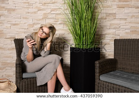 Portrait of a gorgeous young woman wearing glasses and using her cell phone while sitting alone in a waiting area,beautiful blonde hair caucasian female touching her mobile phone - stock photo