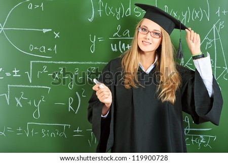 Portrait of a graduating student girl in an academic gown standing at the classroom.