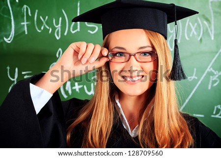 Portrait of a graduating student girl in an academic gown standing at the classroom. - stock photo