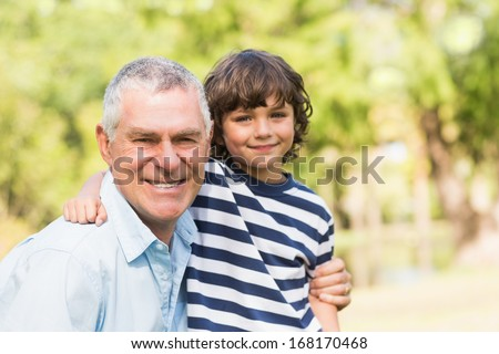 Portrait of a grandfather and son smiling in the park - stock photo