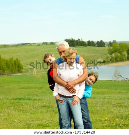 portrait of a grandfather, daughter and granddaughter on the background  attractive landscape. Family of three generations. - stock photo