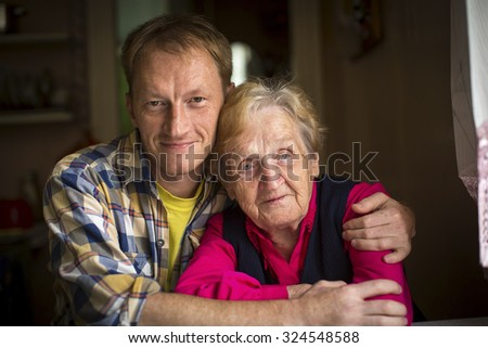 Portrait of a grandmother and her adult grandson. - stock photo