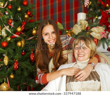 Portrait of a grandmother and teen granddaughter near the Christmas tree being happy and joyful - stock photo