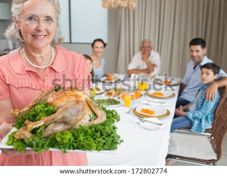 Portrait of a grandmother holding chicken roast with family at dining table in the house
