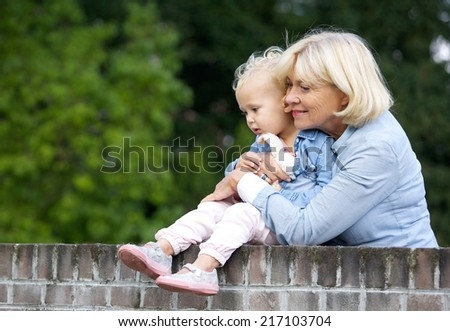 Portrait of a grandmother holding cute baby girl - stock photo