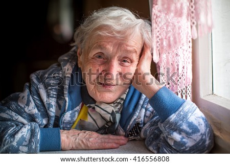 Portrait of a grandmother sitting near the window.