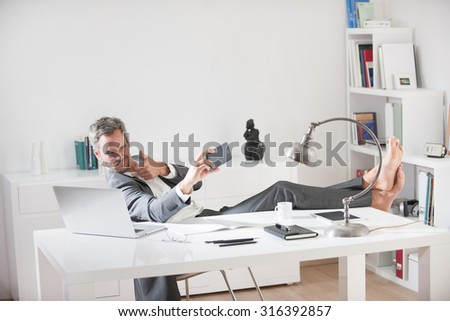 Portrait of a grey hair business man with beard sitting at his desk in a luminous office. He is relaxing, his barefoot on the desk, looking at his smartphone taking selfie. He is wearing a grey suit.