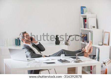 Portrait of a grey hair business man with beard sitting at his desk in a luminous office. He is relaxing, his barefoot on the desk, smiling and speaking on the phone. He is wearing a grey suit.