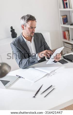 Portrait of a grey hair businessman and beard  working on his tablet at his white desk. He is sitting in a white office with his notebook, his computer, his glasses and some pens next to him.