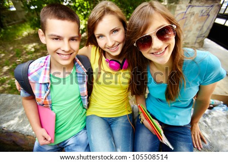 Portrait of a group of good school friends hugging in front of the cam - stock photo