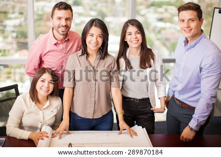 Portrait of a group of Hispanic architects working on a project in a meeting room - stock photo