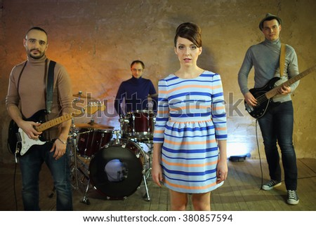 Portrait of a group of musicians with musical instruments and a girl singer - stock photo